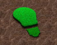 Green grass of light bulb on red soil background royalty free stock photo