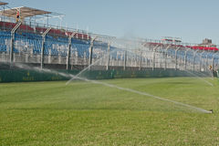 Watering grass at circuit Stock Photos