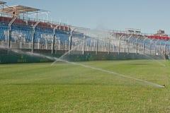 Watering grass at circuit Stock Photos