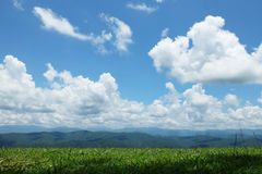 Green grass and mountain under blue sky. With a white cloud, Nan, North of Thailand Stock Photos