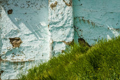 Green Grass Over Blue Cracked Wall Stock Photo