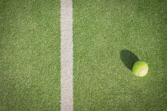 Paddle tennis court and ball. Green grass paddle tennis court and net with a yellow ball on the surface with a tennins racket stock photo