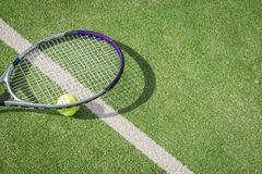 Paddle tennis court and ball. Green grass paddle tennis court and net with a yellow ball on the surface with a tennins racket stock photography