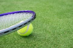 Paddle tennis court and ball. Green grass paddle tennis court and net with a yellow ball on the surface with a tennins racket royalty free stock photography