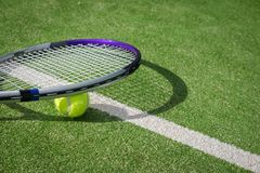 Paddle tennis court and ball. Green grass paddle tennis court and net with a yellow ball on the surface with a tennins racket stock image