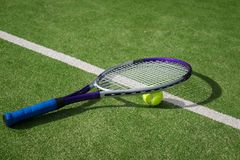 Paddle tennis court and ball. Green grass paddle tennis court and net with a yellow ball on the surface with a tennins racket royalty free stock image