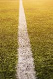 Green grass pattern for football sport, Football field, soccer field, team sport texture. White stripe on it. Close up. Focus. Flare sunlight flare for text and Stock Image
