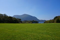 Green grass and mountain on background. Public garden during springtime in Ireland Royalty Free Stock Images