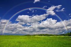 Green Grass Rainbow. Green grass field with rainbow in the background stock photography