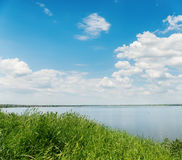 Green grass, river and clouds in blue sky. Summer landscape with green grass, river and clouds in blue sky Royalty Free Stock Photo