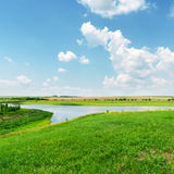 Green grass and river under blue sky Stock Photo