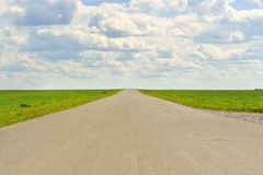 Green grass, road and clouds Royalty Free Stock Photography