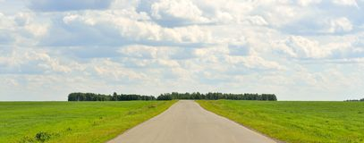 Green grass, road and clouds Royalty Free Stock Photos