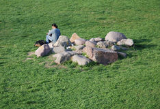 Green grass, rocks and men Royalty Free Stock Photography