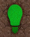 Green grass in the shape of light bulb on dry red soil with cracks background, concept of ECO and renewable energy stock photography