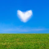 Green grass under blue sky and a heart shape cloud. Beauty nature background Stock Image