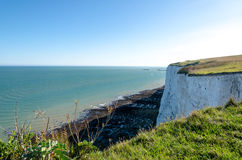 Green grass by the White Cliffs of Dover overlooking the pebble beach and the port Royalty Free Stock Image