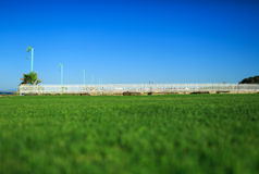 Green grass and white fence on the sea shore. Bright green grass and white fence on the sea shore Royalty Free Stock Photography