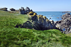 Green grass and Wild coastline in south of Yeu Island. Panorama of Wild Rocky Coastline in South-East of Yeu Island with green grass at foreground. France Royalty Free Stock Photos
