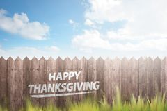 Green grass and wooden fence with text Happy Thanksgiving stock photo