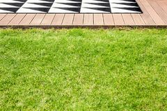 Grass in garden. Green grass and a wooden terrace with geometrical rug in a garden stock photo