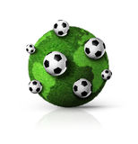 Green grass world globe with soccer balls Royalty Free Stock Images