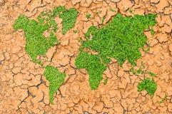 Green grass world map on cracked ground. Green grass world map on cracked clay ground Stock Photos
