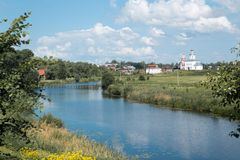 Temple on the river bank in the meadow. Green grass, yellow flowers and tall bushes grow on the left bank of a small river. There is a white temple on the right stock photography