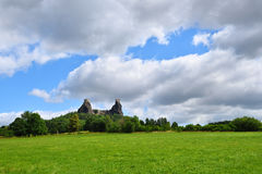 Green grassfield with medieval castle ruins Stock Photography
