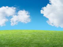Green grassy hill. In a bright blue cloudy sky stock photo