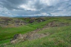 Green, grassy hill. Near the river rocks. Summer season. Nature. stock images