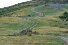 Green, grassy hill. The path, the road on the hill. Summer season. Nature. stock photography