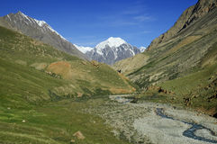 Green grassy mountain valley with stream and hills. In Kuylu mountains, Central Tien-Shan, Kyrgyzstan Stock Photos