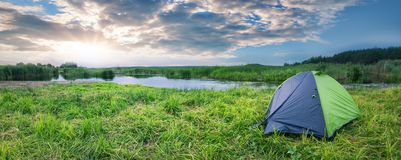 Green and gray tourist tent on the river bank in summer Stock Photos