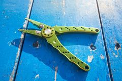 Green gripper on blue wood table Stock Photo
