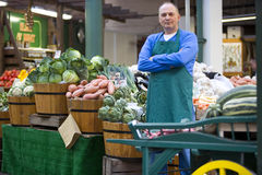 Green grocer with arms crossed by produce, portrait Royalty Free Stock Image