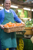 Green grocer with basket of peppers, smiling, portrait stock images