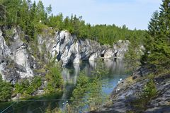 Green groundwater former marble quarry. Fascinating marble canyon. Filled with green groundwater former marble quarry. High cliffs, forest, green marble water stock image
