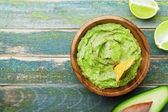 Green guacamole with ingredients avocado, lime and nachos on wooden vintage table top view. Traditional mexican food. stock photography