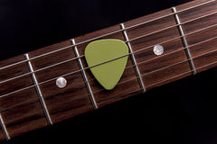 Green guitar pick on the fingerboard. On black background Royalty Free Stock Image