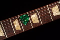 Green guitar pick on the fingerboard and dark. Background royalty free stock images