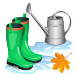 Green gumboots in puddle, gray watering can and falling leaf. Green gumboots in puddle, gray watering can and falling orange maple leaf. Autumn, gardening Stock Photo