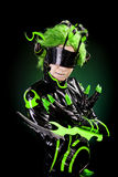 Green haired girl dressed as an insect. Over dark background stock image
