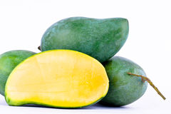 Green half  mango peeled and three fresh  green mangoes on white background healthy fruit food isolated Royalty Free Stock Photography