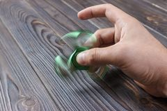 green hand spinner, or fidgeting spinner, rotating on man's hand royalty free stock photos