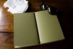 TRAVEL JOURNAL, BRASÍLIA - December 23, 2016: handmade notebook. Green handmade notebook over a table open. Sun glasses and glass decorating stock photos