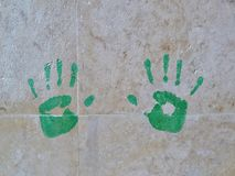 Green handprints on the wall of marble tiles. Close-up royalty free stock photos