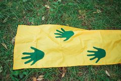 Green handprints on yellow fabric royalty free stock photos