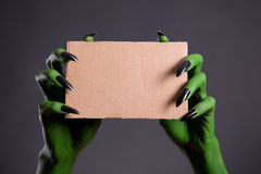 Green hands with black nails holding empty piece of cardboard Stock Images