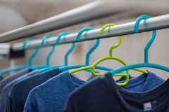 Green hanger Plastic In the clothes array with a blue hanger Plastic. stock photography